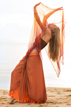 Woman Doing An Oriental Dance On The Beach