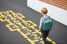A Boy Walking Up To A Hopscotc...