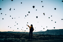 Female In Rocky Terrain With Air Balloons