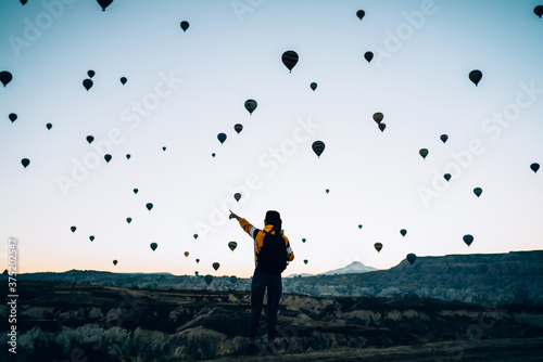 Photo Female in rocky terrain with air balloons