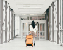 Girl With A Suitcase In A Hall...