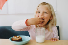 Little Girl Dipping Snack Into Glass Of Milk