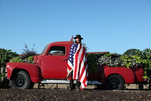 Americana Portrait Of A Cowboy Infront Of A Vintage Truck Wrapped In An American Flag