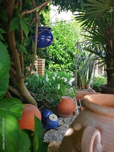 Fototapeta premium Widok na patio ze śródziemnomorską roślinnością. Akcenty w stylu prowansalskim. Ceglasty mur otoczony zielenią.