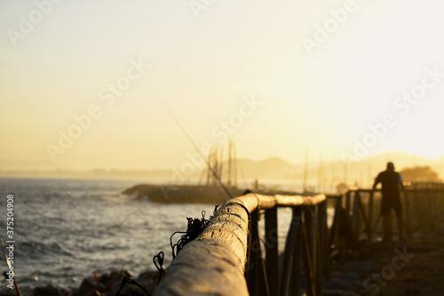 Fényképezés Atardecer con cañas de pescar y madera