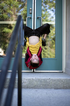 Silly Child Hangs Upside Down On The Doors Of A School