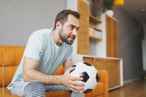Cuadros en Lienzo Nervous young bearded man football fan 20s wearing basic blue t-shirt cheer up support favorite team with soccer ball looking aside sitting on couch resting spending time in living room at home