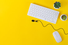 Office Desk Table With Keyboard, Mouse, Microphone And Plants Top View On Yellow Background