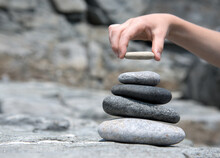 A Child's Hand Places A Rock O...