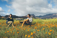 Couple Enjoying Breakfast Picnic Amongst Flowers