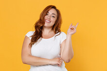 Smiling Young Redhead Plus Size Body Positive Female Woman Girl 20s In White Casual T-shirt Posing Pointing Index Finger Up On Mock Up Copy Space Isolated On Yellow Color Background Studio Portrait.