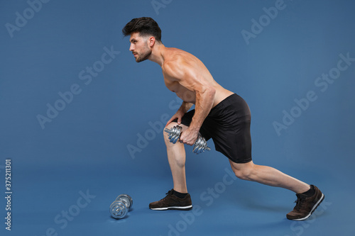 Fotografie, Tablou Full length portrait side view of young fitness strong guy bare-chested muscular sportsman isolated on blue background