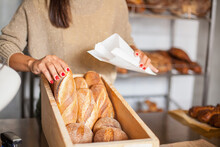 Woman Packing Bread In A Bakery