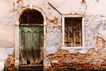 A Doorway And Window In A Decaying Wall In Venice, Italy