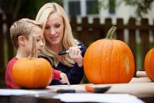 Pumpkins: Mother And Child Work On Jack-O-Lantern Face