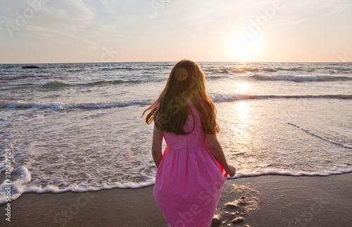 Girl in pink dress standing at ocean's edge facing sunset - 375217723