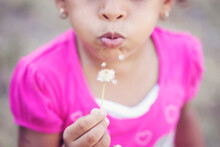 Closeup Portrait Of A Young Girl Blowing A Dandelion Puff