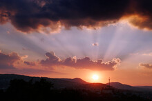 Setting Sun With Twighlight Rays Above Hills
