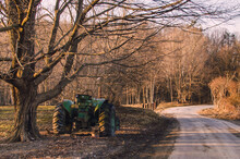 Green Tractor Parked Under A Tree By A Country Road
