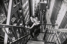 Hispanic Couple Dancing Tango In New York Fire Escape Stairs In Black And White
