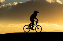 Boy Riding BMX Bike At Sunset