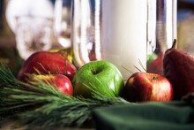 Apples, Pears And Pine Needles Make Up A Table Centerpiece.