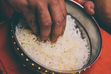 Hand Picking Rice From A Bowl
