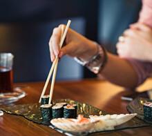 Woman Eating Maki Sushi
