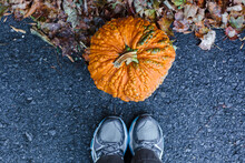 Feet Standing In Front Of A Pumpkin With Warts.
