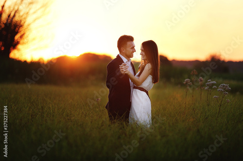 young couple in love are hugging outdoors in the field at sunset on summer day Wallpaper Mural