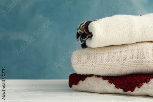 Papel de parede Pile of sweaters on white wooden table against blue background