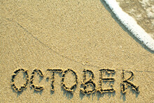 October Inscription On The Sand Beach With The Soft Wave.