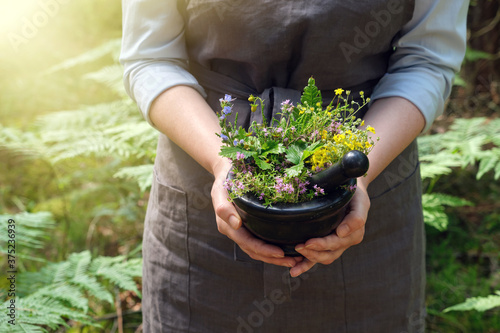 Foto Woman holding in her hands a mortar of medicinal herbs