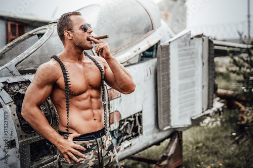 Old war airplane in the abandoned airport and brutal naked soldier near it. American bodybuilder smoking cuban cigar in the field.