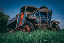 Old Rusted Truck Falling Apart In Green Grass. Retro Truck In The Middle Of A Field