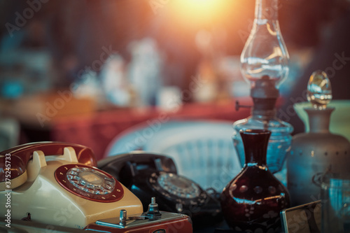 Vintage telephones, oil lamps, vases and bottles on the countertop at the sunday flea market Fototapeta