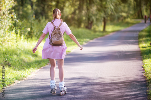 Sporting girl roller skating in a park on summer day. Canvas Print