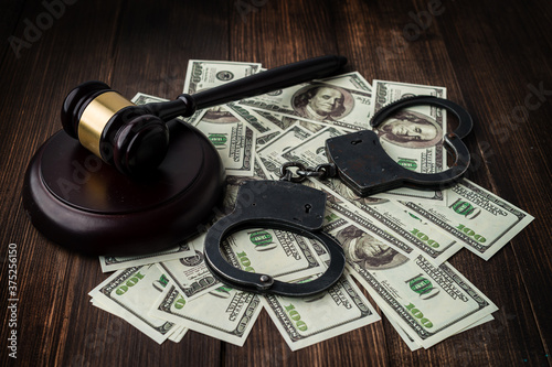 Photo Judge's gavel with handcuffs on the background of dollar bills.