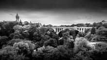 Black And White Photo Of The Pont Adolphe (Adolphe Bridge) And Vallé De La Pétrusse (Petrusse Park) With The Tower Of Musée De La Banque In The City Of Luxumbourg