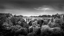 Black And White Photo Of The Pont Adolphe (Adolphe Bridge) And Vallé De La Pétrusse (Petrusse Park), With  A Lightning Strike In The Distance In The City Of Luxumbourg