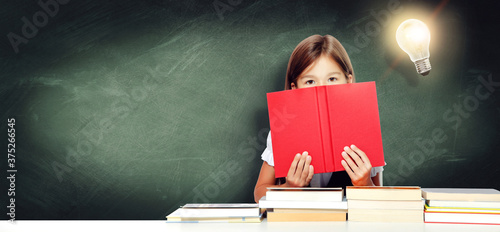 Foto Young cute girl at chalkboard with light bulb over head