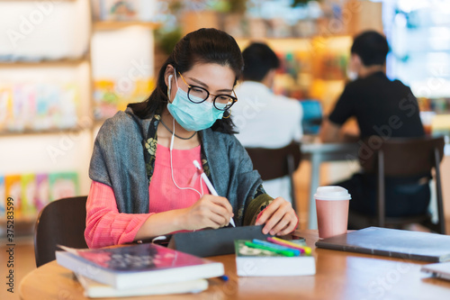 Asian woman wear protective face mask use tablet in public space
