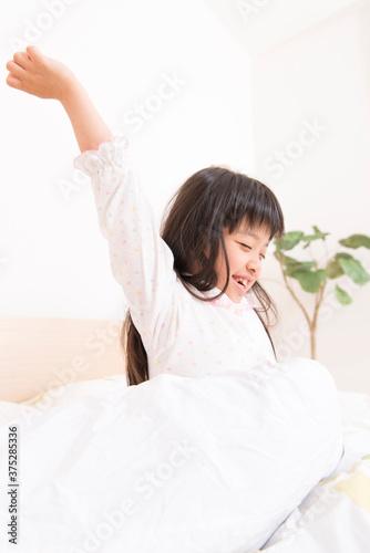 ベッドから起きる女の子 Fototapet