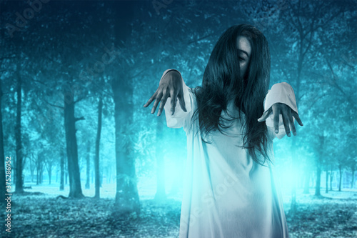Scary ghost woman standing with haunted forest background Fototapeta