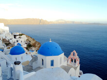 Famous Greek Orthodox Blue Domed Church And Bell Tower In Oia Village On Santorini Island, One Of Famous Greek Aegean Islands.  Travel Destination In Santorini, Greece.