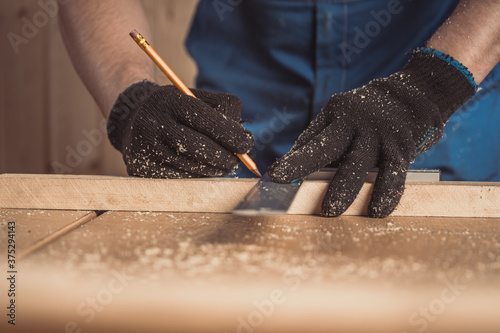 Fotografiet CLose up of the carpenter with a pencil and tape measure mark on wooden board on table