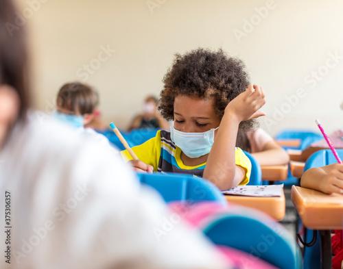Tela school boy wearing  mask and study in classroom
