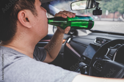Obraz na plátně Young asian man drives a car with drunk a bottle of beer behind the wheel of a c