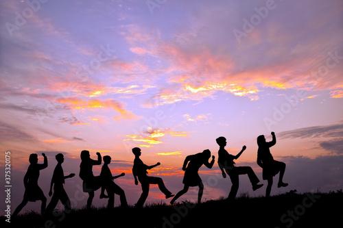 Fototapeta 夕陽を背景に元気よく歩く多数の男女高校生のシルエット