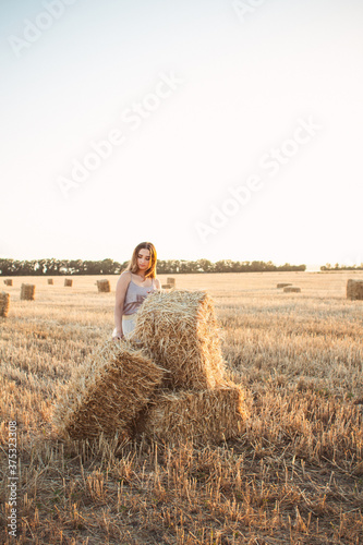 Canvastavla young woman lean on haystack walking in summer evening, beautiful romantic girl